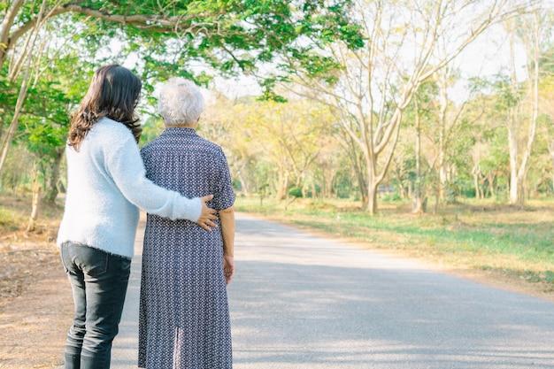 Pomoc i opieka azjatycka starsza kobieta podczas gdy chodzący przy parkiem.