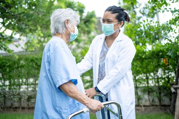 Pomoc i opieka azjatycka starsza kobieta używa chodzika podczas chodzenia po parku