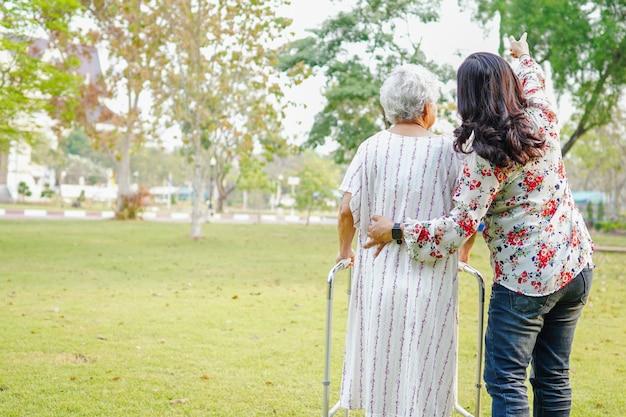 Pomoc i opieka azjatycka starsza kobieta używa piechura w parku.