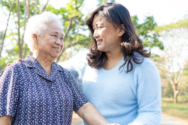 Pomoc i opieka azjatycka starsza kobieta używa walkera w parku.