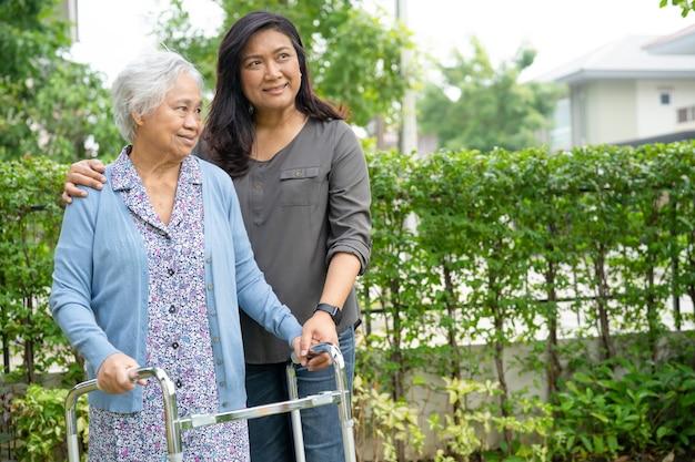 Pomoc i opieka azjatycka starsza lub starsza pani używa chodzika z silnym zdrowiem podczas spaceru po parku w szczęśliwe świeże wakacje.