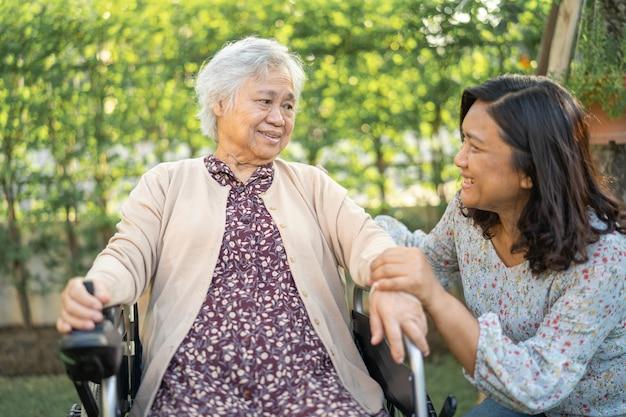 Pomoc i opieka azjatyckiego starszego pacjenta siedzącego na wózku inwalidzkim w parku