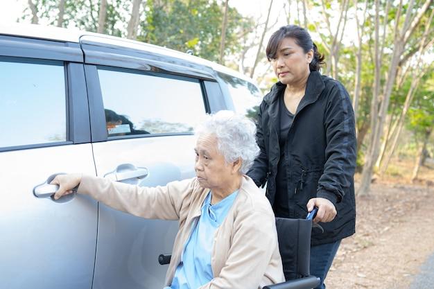Pomoc i wsparcie azjatyckie starsze kobiety cierpliwe, siedząc na wózku inwalidzkim przygotować się do jej samochodu