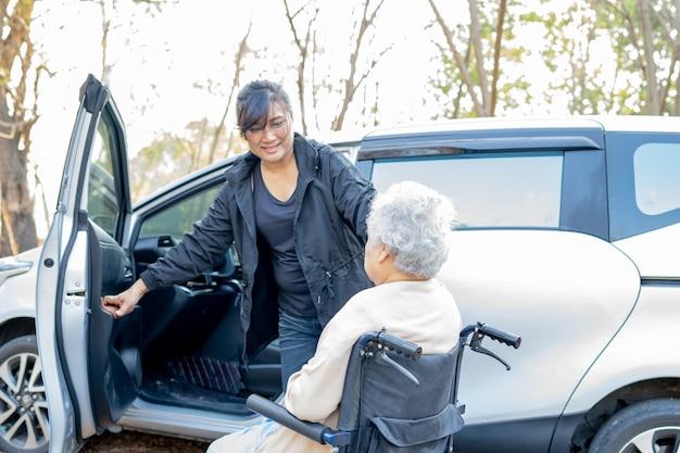 Pomoc i wsparcie azjatyckie starsze kobiety cierpliwe, siedząc na wózku inwalidzkim przygotować się do jej samochodu.