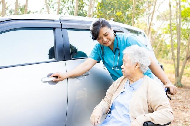 Pomoc i wsparcie azjatyckiej starszej kobiety na wózku inwalidzkim przygotować się do jej samochodu.