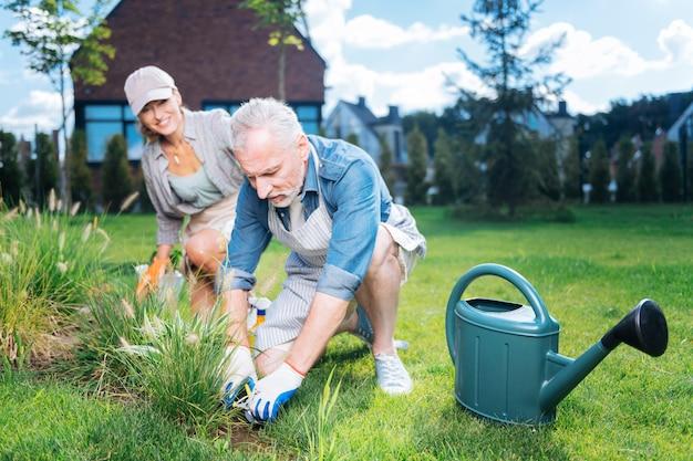 Pomoc i wsparcie. brodaty siwowłosy mąż wspiera i pomaga swojej pięknej promieniejącej żonie w ogrodowym łóżku