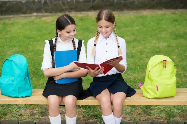 Pomoc i wsparcie. dzieci czytają notatnik do robienia notatek. szczęśliwe dzieciństwo. powrót do szkoły. nastoletnich uczniów gotowych do lekcji. przygotować się do egzaminu. uczyć się razem na świeżym powietrzu. małe dziewczynki z książkami i plecakami.