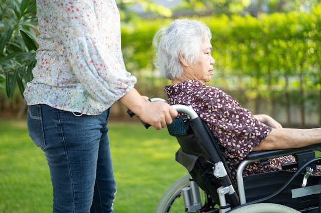 Pomoc lekarza i opieki azjatycki starszy lub starszy pacjent starsza kobieta siedzi na wózku inwalidzkim w parku w oddziale szpitala pielęgniarskiego, zdrowe silne pojęcie medyczne.