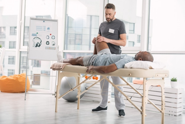 Pomoc medyczna. poważny, wykwalifikowany lekarz masuje nogę pacjenta podczas rozwijania mięśni