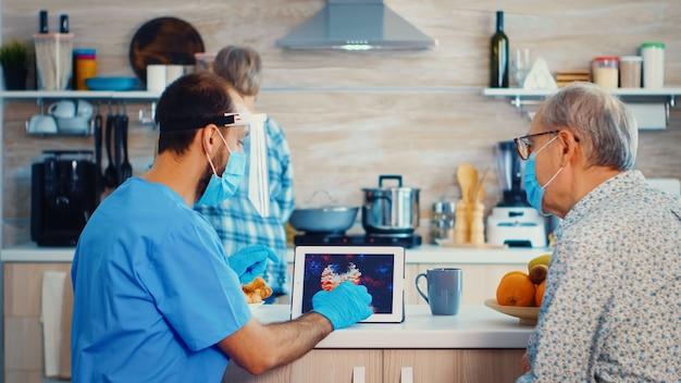 Pomoc medyczna wskazująca obraz koronawirusa na komputerze typu tablet podczas wizyty domowej. pielęgniarz, pracownik socjalny podczas wizyty emerytowanej pary seniorów, wyjaśniającej rozprzestrzenianie się covid-19, pomoc dla osób z grupy ryzyka