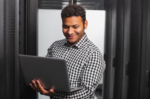 Pomoc techniczna. wesoły facet it za pomocą laptopa i uśmiechnięty