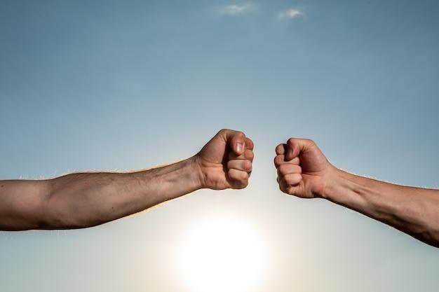 Pomocna dłoń. dwie ręce wyciągnięte do siebie na tle błękitnego pochmurnego nieba.