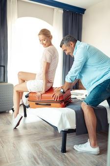 Pomocna dłoń. uśmiechnięta kobieta siedząca na walizce, pomagająca skoncentrowanemu mężowi w pakowaniu i zamykaniu walizki.