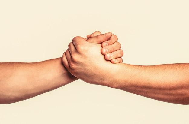 Pomocna dłoń wyciągnięta, odizolowane ramię, zbawienie. przyjazny uścisk dłoni, powitanie przyjaciół, praca zespołowa, przyjaźń. ratunek, pomocny gest lub dłonie.
