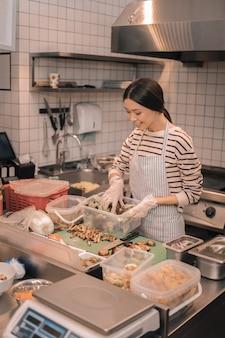 Pomocna kelnerka. widok z góry na atrakcyjną kelnerkę pomagającą w krojeniu potraw w kuchni