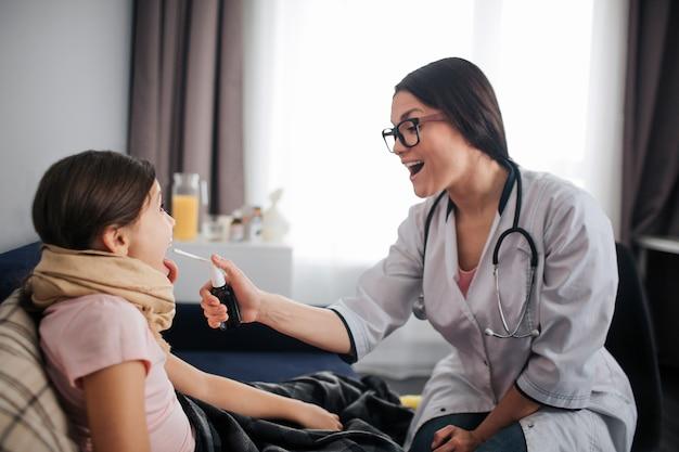 Pomocna młoda lekarz emale siedzieć obok pacjenta w pokoju. trzyma spay za ból gardła