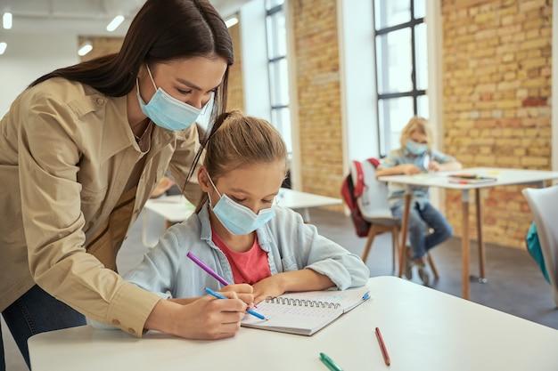 Pomocna młoda nauczycielka nosząca maskę ochronną, pomagająca małej dziewczynce robić sumy dzieciom