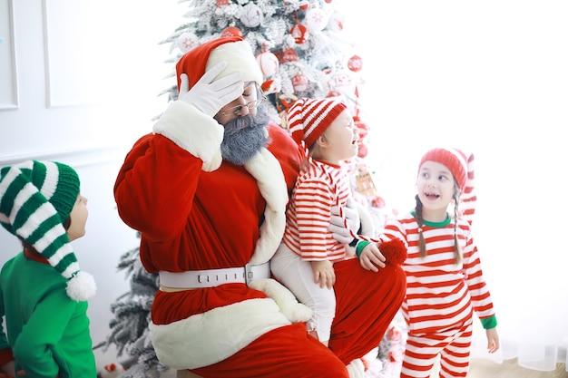 Pomocnicy świętego mikołaja. słodkie dzieci w strojach świątecznych elfów w pokoju pięknie udekorowanym na boże narodzenie. czas cudów. prezenty od świętego mikołaja.