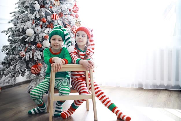 Pomocnicy świętego mikołajasłodkie dzieci w strojach świątecznych elfów prezenty od świętego mikołaja