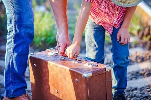 Pomocnik ojca i syna trzymają walizkę w pobliżu linii kolejowej