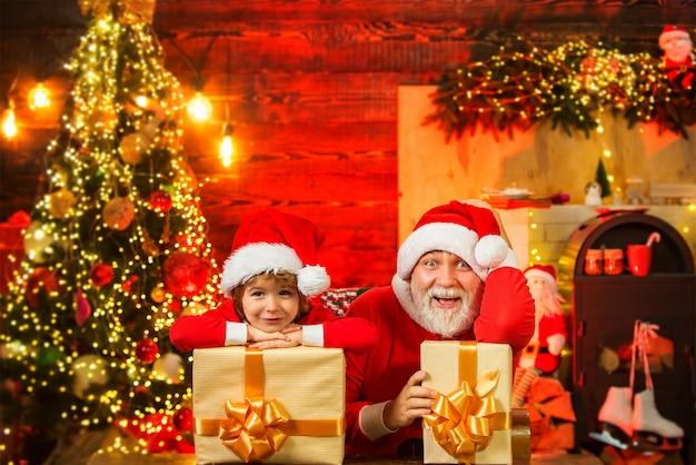 Pomocnik świętego mikołaja i święty mikołaj z prezentem na boże narodzenie