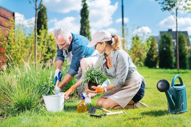 Pomocny człowiek. pomocny dojrzały mężczyzna dołącza do swojej pięknej żony podczas karczowania chwastów na grządce ogrodowej przed ich domem