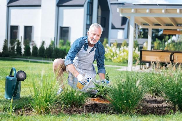 Pomocny mąż. pomocny mąż zraszający wodą zielone rośliny w ogrodzie przed domem jednorodzinnym