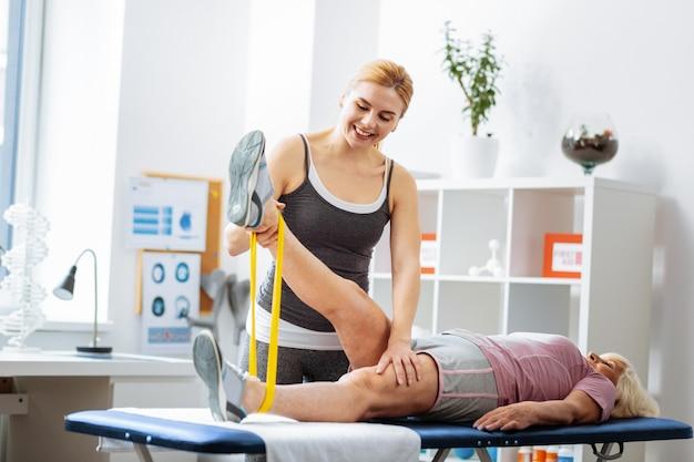 Pomocny personel. pozytywna młoda kobieta trzymająca nogę pacjenta podczas ćwiczeń fizycznych