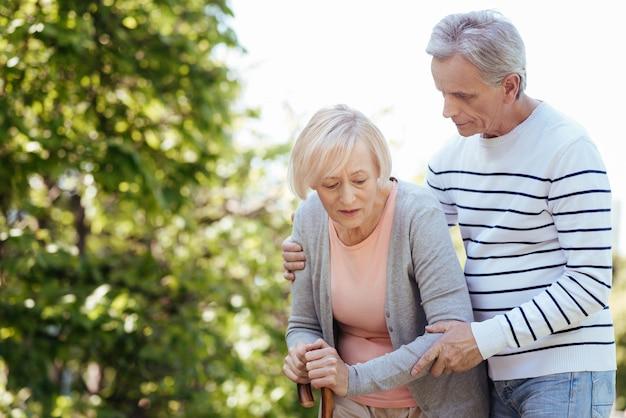 Pomocny, troskliwy, życzliwy mężczyzna opiekujący się swoją sędziwą żoną i pomagający jej stawiać kroki podczas spaceru po parku
