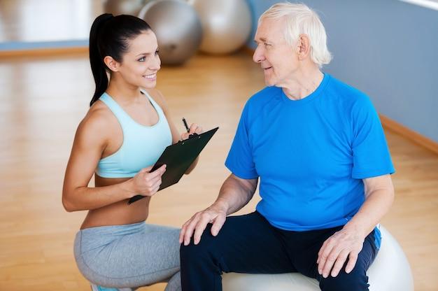 Pomogę ci w powrocie do zdrowia. pewny siebie fizjoterapeuta trzymający schowek i uśmiechający się, siedząc blisko starszego mężczyzny