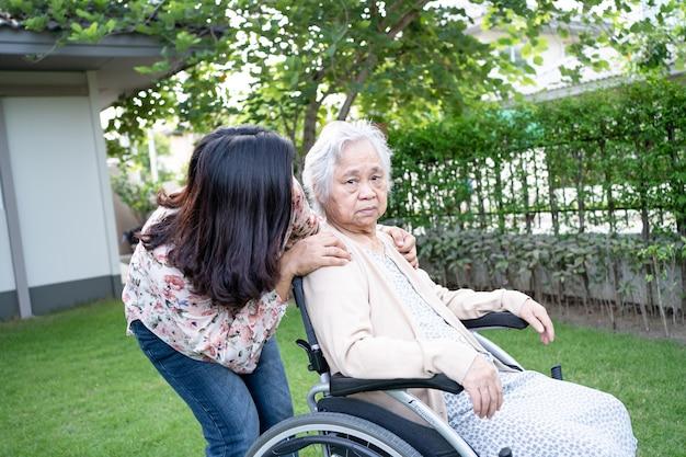 Pomóż azjatyckiej pacjentce starszej kobiety na elektrycznym wózku inwalidzkim w parku