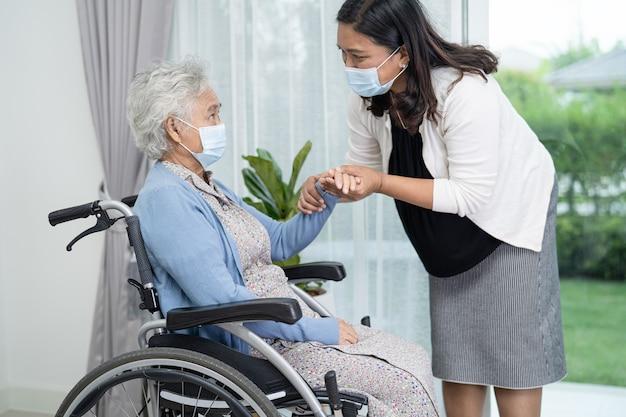 Pomóż azjatyckiej starszej kobiecie siedzącej na wózku inwalidzkim i noszącej maskę w celu ochrony przed zakażeniem koronawirusem