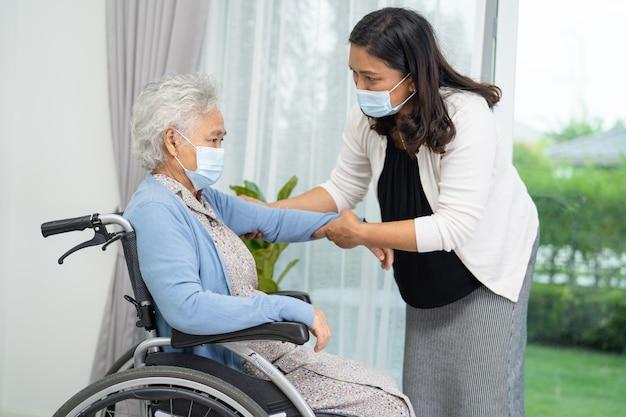Pomóż azjatyckiej starszej lub starszej starszej kobiecie siedzącej na wózku inwalidzkim i noszącej maskę na twarz