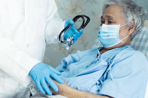 Pomóż lekarzowi starszej pacjentce z azji noszącej maskę na twarz w celu ochrony koronawirusa covid-19.