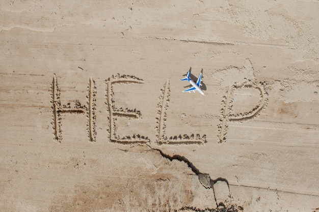Pomóż mi napis i samolot na piasku pomóż mi na tropikalnej plaży