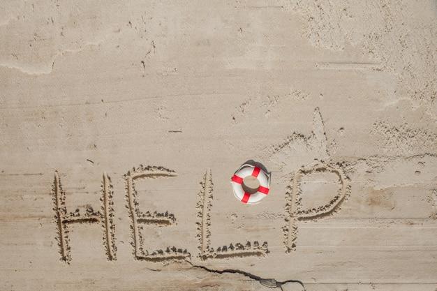 Pomóż mi napis na piasku. proszę pomóż mi. na tropikalnej plaży.