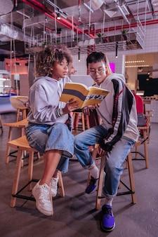 Pomóż mi. uważne kręcone włosy dziewczyna trzyma książkę w obu rękach podczas czytania zadania