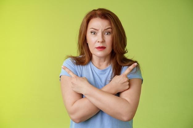 Pomóż mi wybrać zmartwiony niepewny wątpliwy słodka rudowłosa w średnim wieku głupia kobieta prosząca o radę krzyż ramiona ciało skierowane w bok w lewo w prawo spojrzenie zaniepokojone aparat podjęcie trudnej decyzji zielona ściana