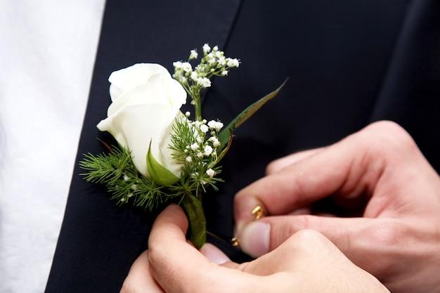 Pomóż panu młodemu przypiąć ślubny kwiat do garnituru. akcesoria wakacyjne