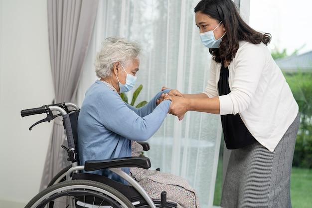 Pomóż starszej azjatyckiej kobiecie siedzącej na wózku inwalidzkim i noszącej maskę w celu ochrony przed koronawirusem