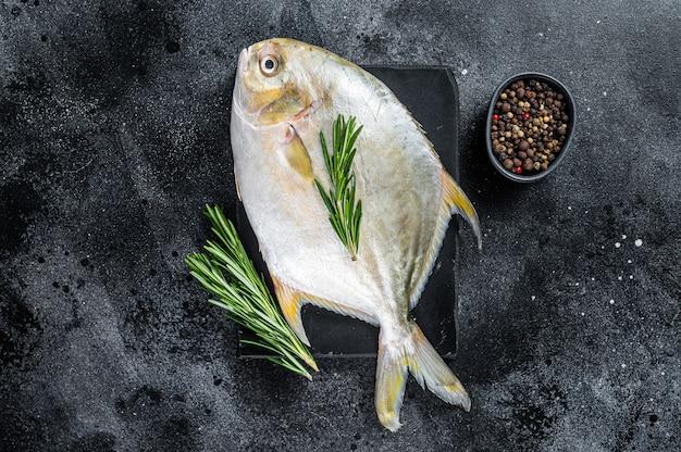 Pompano surowej ryby z ziołami na marmurowej desce