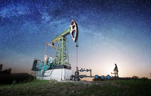 Pompy do oleju pracują na polu naftowym wieczorem