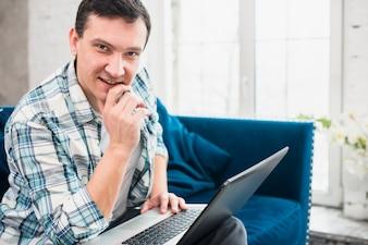 Pomyślny męski używa laptop na kanapie w domu