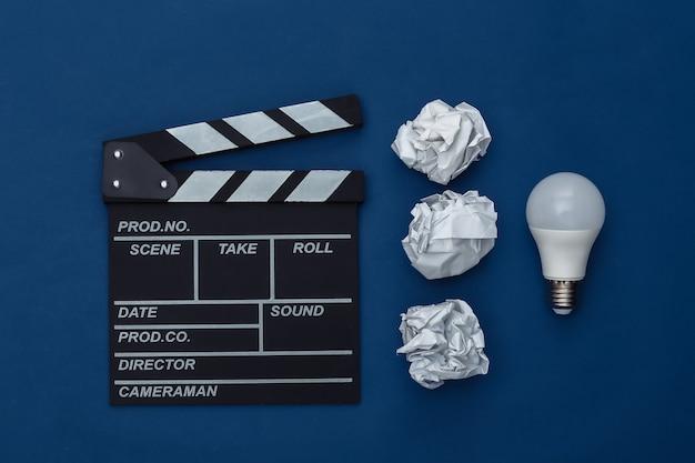 Pomysł! film clapper deska z zmiętymi papierowymi kulkami, żarówka na klasycznym niebieskim tle. produkcja filmowa, produkcja filmowa. kolor 2020. widok z góry