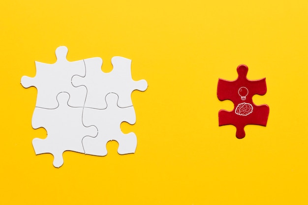 Pomysł ikona na czerwonym kawałku układanki stoi blisko białego wspólnego łamigłówka kawałka nad żółtym tłem