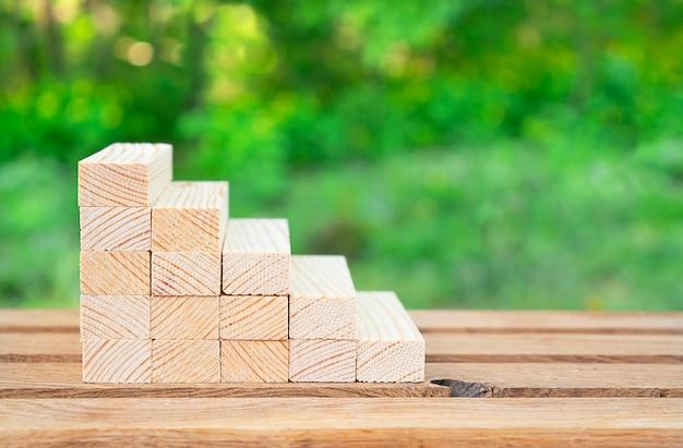 Pomysł na biznes. drewniane schody na stole z zielonym bokeh