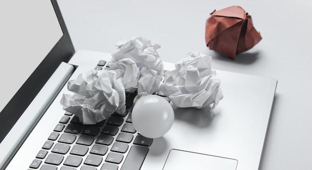 Pomysł na biznes koncepcji. laptop, zmięte papierowe kulki, żarówka led na szarym stole
