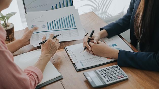 Pomysł na biznes. ludzie biznesu omawiają wykresy przedstawiające wyniki ich udanej pracy zespołowej.