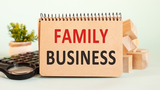 Pomysł na biznes. notatnik z tekstem biznes rodzinny arkusz białego papieru na notatki, kalkulator, bloki drewniane, lupa, na tle