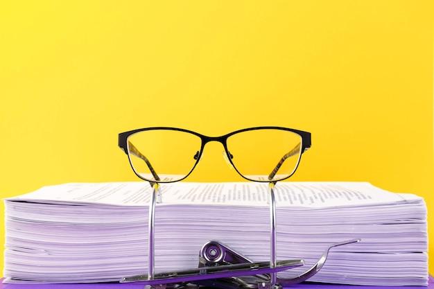 Pomysł na biznes. okulary w folderze z plikami w biurze na żółtym tle. skopiuj miejsce.
